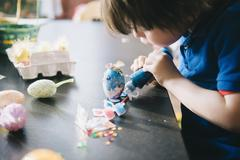 A child decorating eggs at Easter with glitter, glue and paint. Stock Photos