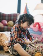 A boy unwrapping his presents at his birthday party. Stock Photos