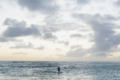 Man stand up paddling in calm waters at dusk Stock Photos