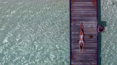 Model tanning on jetty in the crystal clear water in Maldives- 4K Drone Video - stock footage