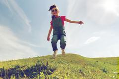 Happy little girl jumping high outdoors Stock Photos