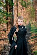 Sad girl with a lowered head near the forest road. Beautiful woman in black d - stock photo