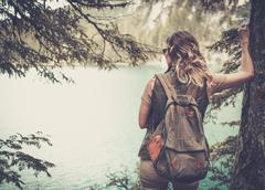 Woman hiker with backpack enjoying amazing mountain lake landscapes Stock Photos