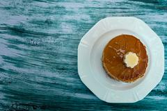 Top view of pancakes with butter and honey or maple syrup on white plate on b - stock photo