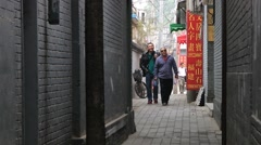 People walk by a narrow side street in Beijing, China. Stock Footage