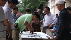 Man performs calligraphy on paper at the street in Beijing, China. Stock Footage