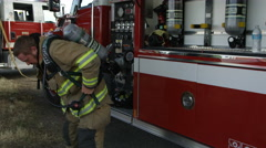 Fireman putting on oxygen tank making funny face Stock Footage