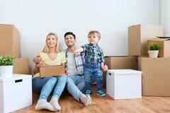 happy family with boxes moving to new home - stock photo