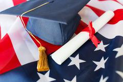 bachelor hat and diploma on american flag - stock photo