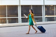 happy young woman with travel bag and map in city - stock photo