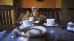 A little happy girl is sitting on the couch at a cafe and hugging her stuffed - stock footage