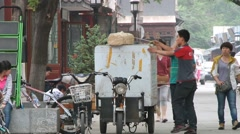 Deliveryman fixes parcel on a motorbike at the street in Beijing, China. Stock Footage