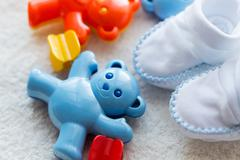 close up of baby rattle and bootees for newborn - stock photo