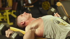 Man performs exercise lifting dumbbells for biceps lying on bench Stock Footage