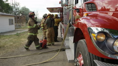 Firemen next to fire truck gearing up Stock Footage