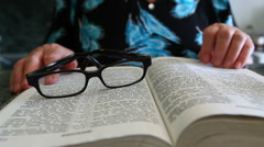 Adult old woman with glasses finished to read the Bible Stock Footage