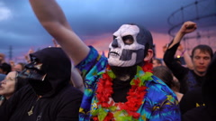 A rock fan in the mask of death hangs out at a rock concert. Stock Footage