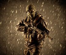 Dangerous heavily armed terrorist soldier with mask on grungy rainy backgroun - stock photo