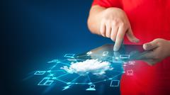 Close up of hand holding tablet with cloud network technology - stock photo