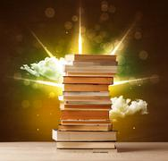 Magical books with ray of magical lights and colorful clouds Stock Photos