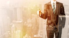 Business man looking at overlay city background - stock photo