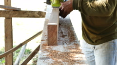 Worker planing a plank of wood with a electric plane Stock Footage