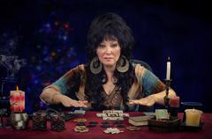 Clairvoyant doing fortune telling cards reading  at the desk Stock Photos