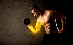 Muscular bodybuilder lifting weight with flaming biceps concept - stock photo