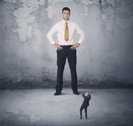 Big business bully looking at small coworker Stock Photos