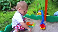 A child plays in the sandbox with the car. Stock Footage