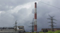 High-voltage power lines, from the chimney power plant emits smoke - stock footage