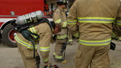 Firemen next to fire truck getting gear on - stock footage