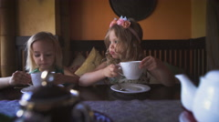 Two cute little blonde girls are having tea in a cozy cafe - stock footage