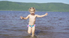 Slow motion. Little girl running, jumping, playing in the water. River bank, Stock Footage