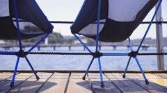 Small assembled camping chairs standing alone at sea 4K Stock Footage