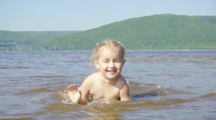 Slow motion.Little girl plays in the water in the river on a sandy bank. Happ Stock Footage