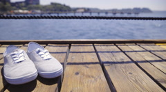 Cute textile shoes sliding over on wooden pier 4K Stock Footage