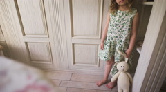 A cute little girl standing in a white room holding a stuffed rabbit Stock Footage