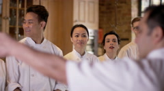 4K Professional chef talking to happy young trainees in cookery school Stock Footage