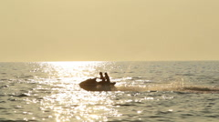 Young couple on a jet ski passing under the sun Stock Footage