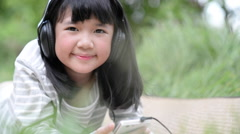 Beautiful asian girl listening music in the park Stock Footage
