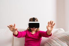 Girl wearing virtual reality goggles. Studio shot, copy space - stock photo
