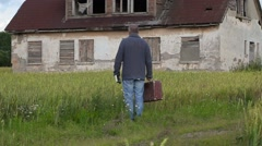 Man with suitcase looking to old abandoned home and walking away - stock footage