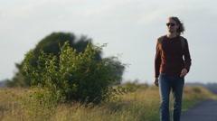4K Lone man walks along an empty country road - stock footage