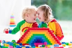 Kids playing with colorful blocks - stock photo