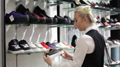 Shopping in the mall - woman choosing a pair of boots Stock Footage