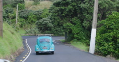 Cars driving down the road in KareKare, Auckland, New Zealand Stock Footage