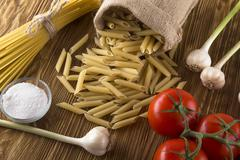 Raw pasta and ingredients with tomatoes , garlic , salt Stock Photos