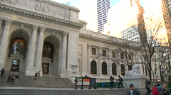 Pedestrians walk in front of NY Public Library on Fifth Avenue, pan left - stock footage
