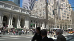Executives cross Fifth Ave. after a cyclist passes in front of NY Public Library Stock Footage